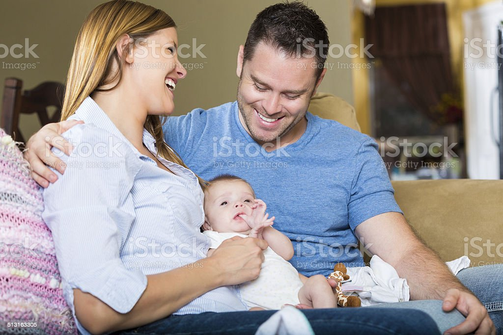 Proud happy parents smiling while holding infant daughter at home stock photo