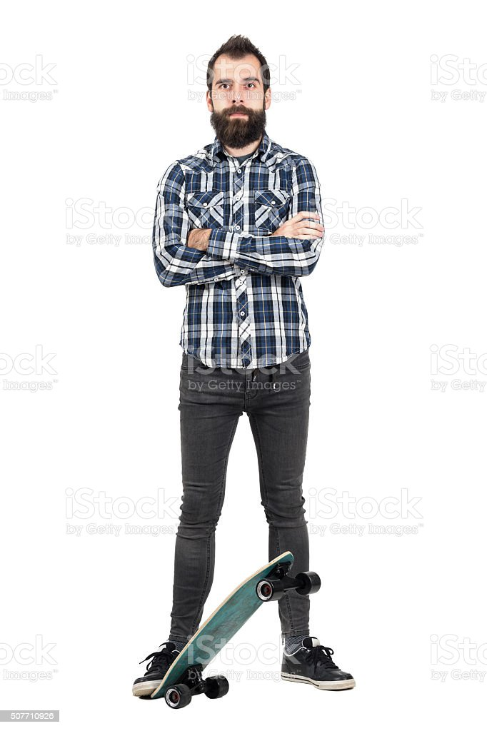 Proud hipster wearing tartan plaid shirt standing on skateboard stock photo