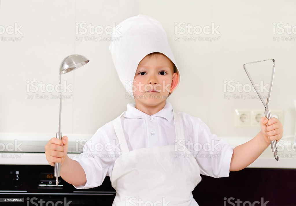 Proud little boy chef in a white toque stock photo