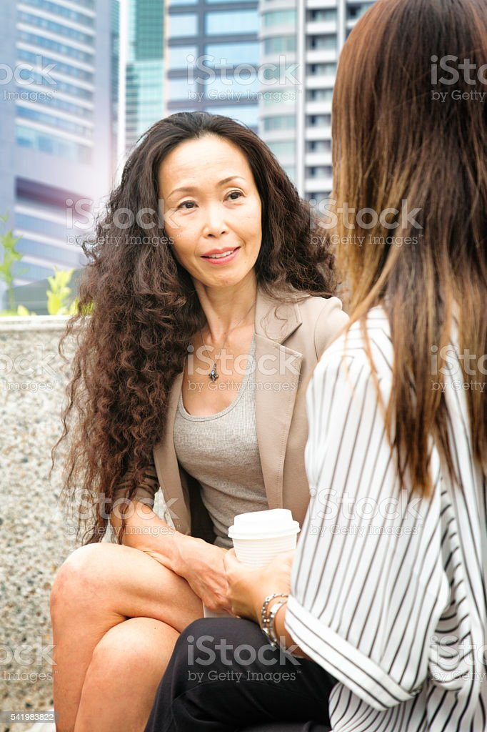Proud mature female Japanese  businesswoman smiles at her protegee stock photo