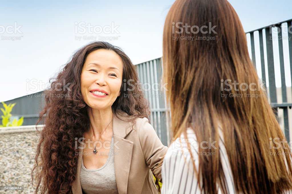 Proud mature female Japanese  mentor smiles at her protegee stock photo