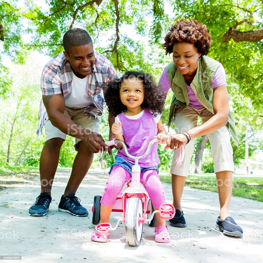 Proud parents teach daughter to ride tricycle stock photo