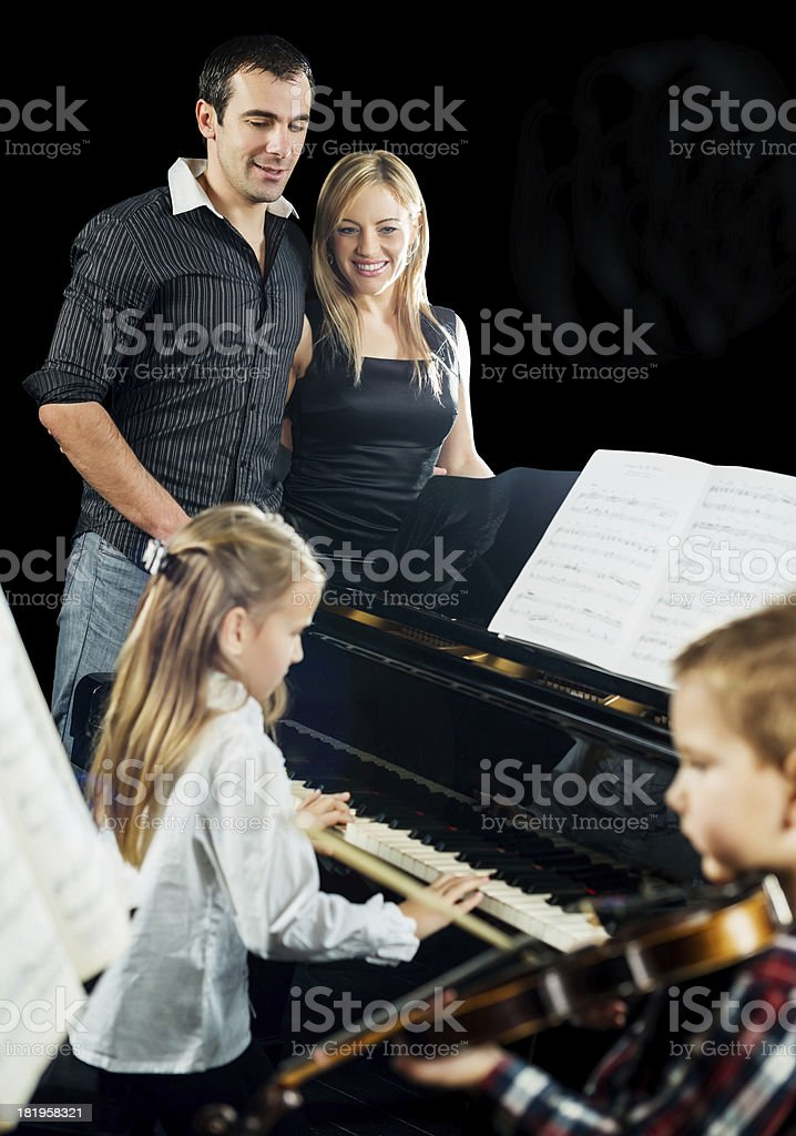 Proud parents watching their children playing musical instrument royalty-free stock photo