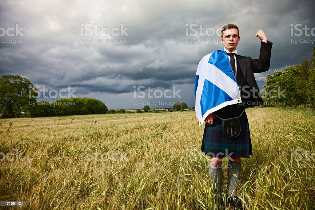 Proud scotsman in cornfield with kilt and saltire stock photo