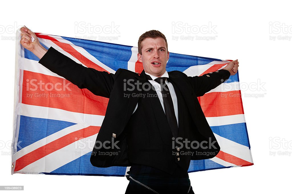 Proud scotsman in kilt holding Union Jack aloft stock photo