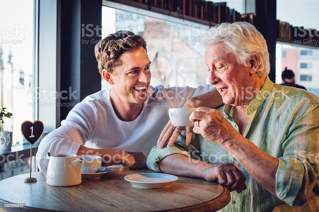 Proud son enjoying a coffee with his mature dad stock photo