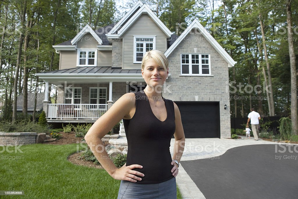 Proud Wife In Front Of Her family House stock photo