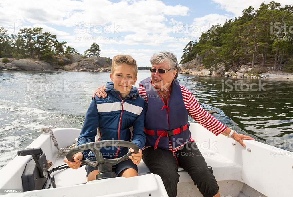 Proud young captain running small motor boat with grandmother. stock photo