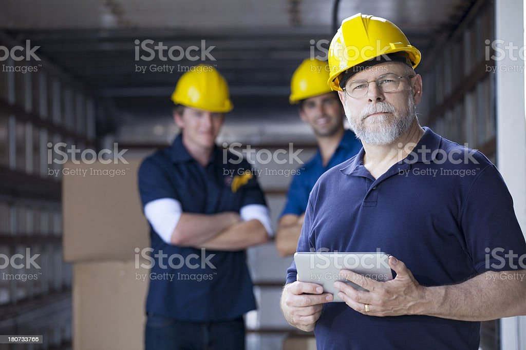 Pround foreman standing in front of his team royalty-free stock photo