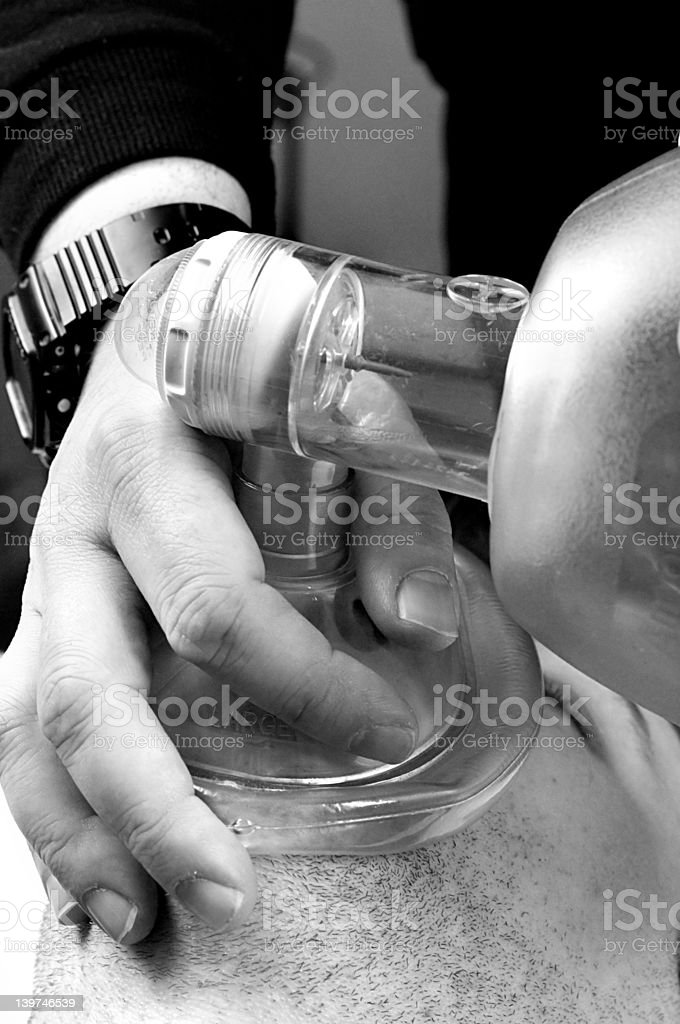 Providing artificial ventilation with BVM (bag-valve-mask) B&W stock photo