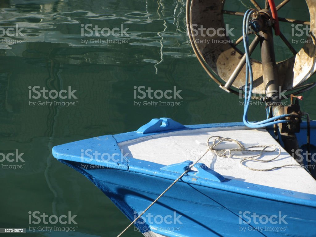 Prow of a wooden fishing boat with trawl winch on the deck . The fishing boat is moored in the harbor . Tuscany, Italy stock photo
