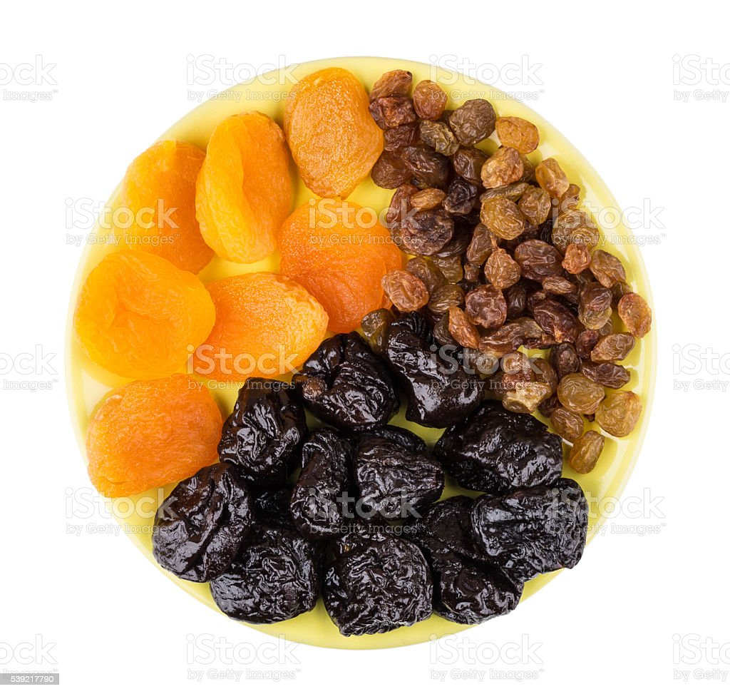 Prunes, driet apricots and raisins in saucer isolated on white stock photo