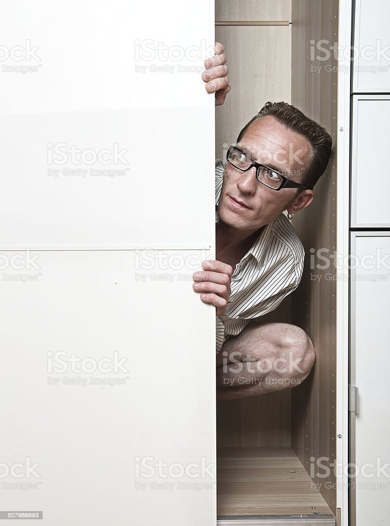Prying man hiding inside white wardrobe. stock photo