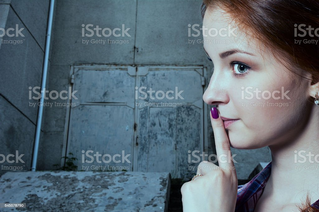 Psst - a beautiful girl with pigtails making stock photo