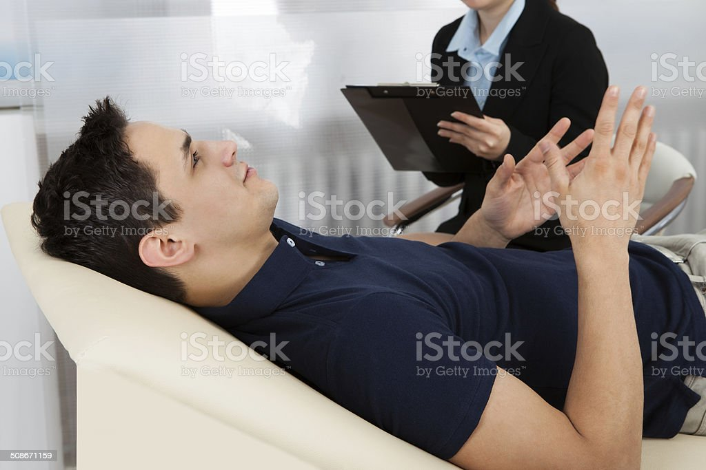 Psychologist Writing Notes While Patient Lying On Bed stock photo
