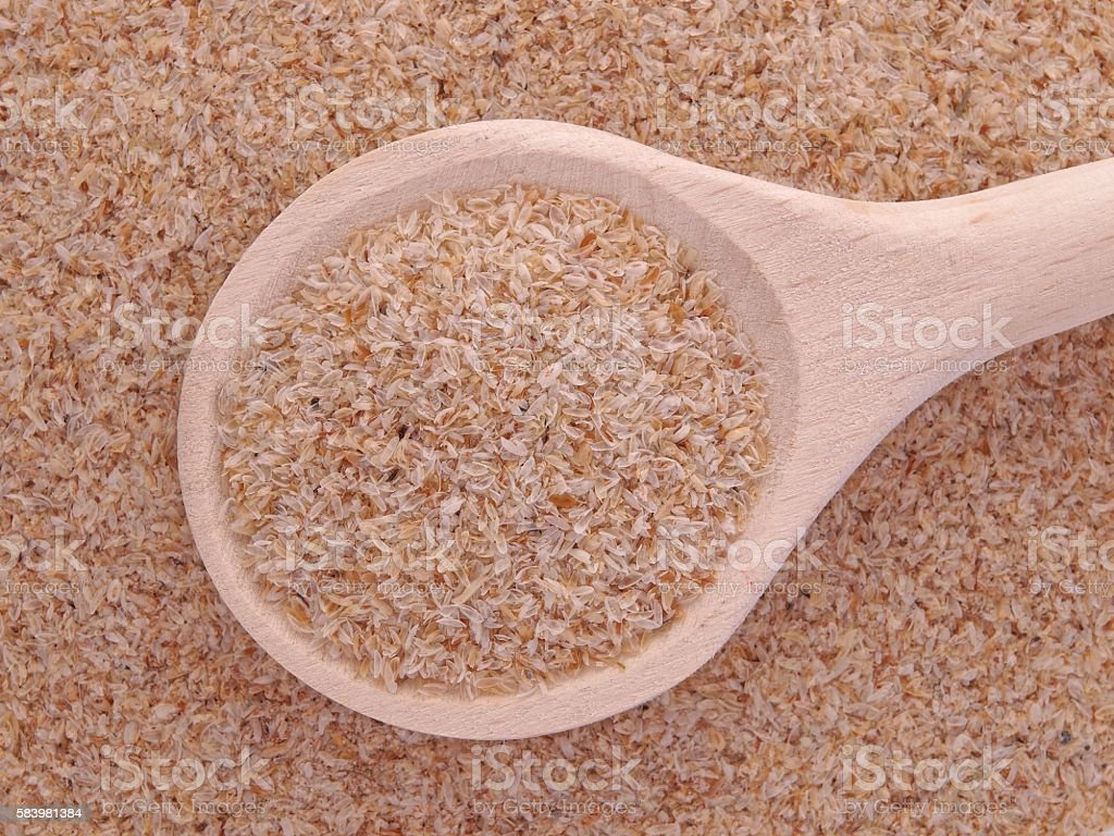 Psyllium seeds husks in wooden spoon stock photo