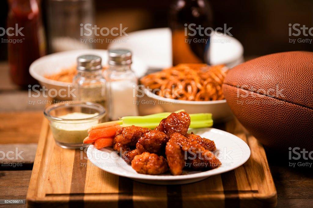 Pub food. Snacks, beer, football. Spicy chicken wings. stock photo