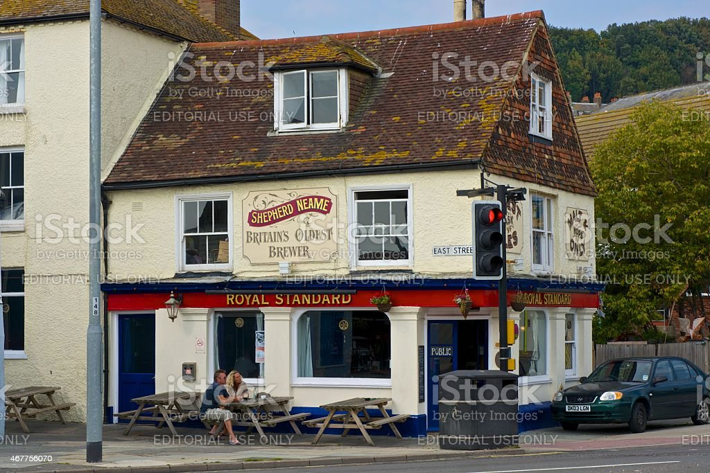 Pub in Hastings old town with people seated outside. England stock photo