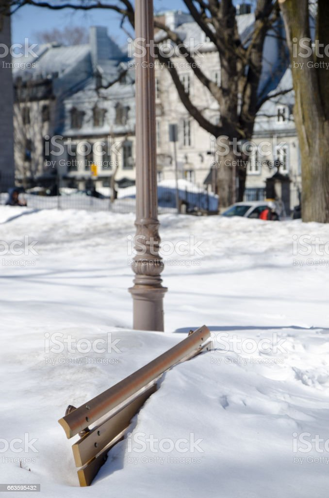 Public bench under snow with lamp post on Ste-Anne Street stock photo