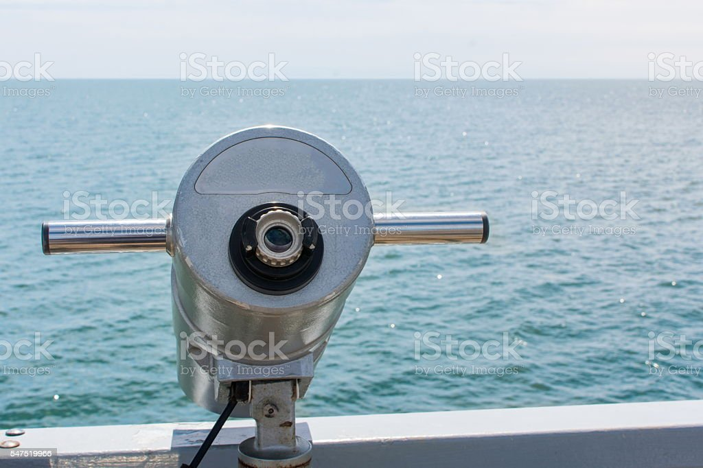 Public binoculars looking at the sea and horizon stock photo