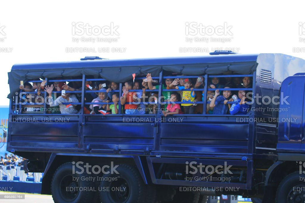 Public citizens enthusiastically boarded troop trucks stock photo