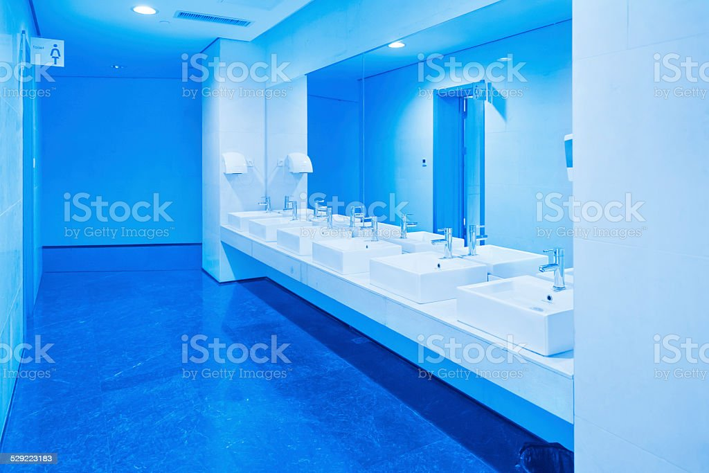 Public empty restroom with washstands mirror stock photo