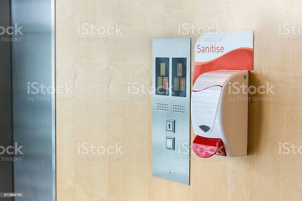 Public hand sanitizer next to elevator stock photo