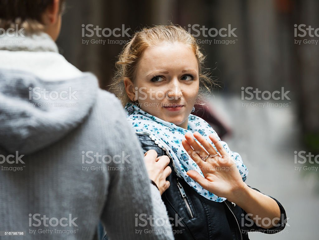 Public harassment: man chasing irritated girl stock photo