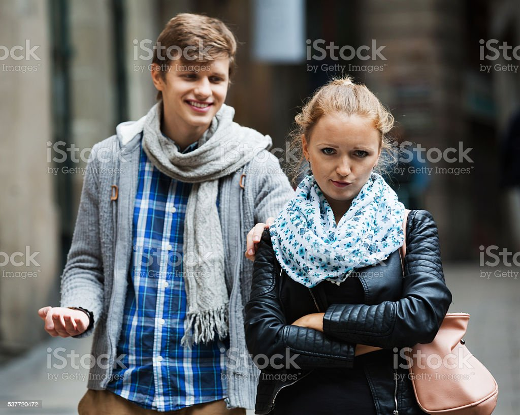 Public harassment: man chasing  irritated girl stock photo