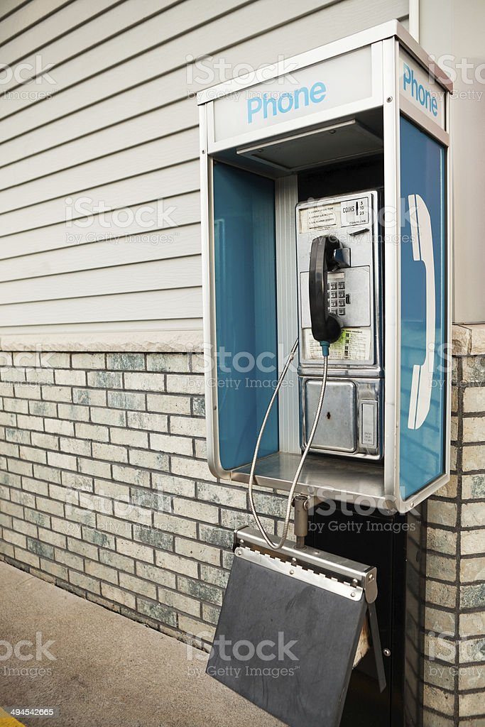 Public Pay Phone Booth with Phone Book next to Building stock photo