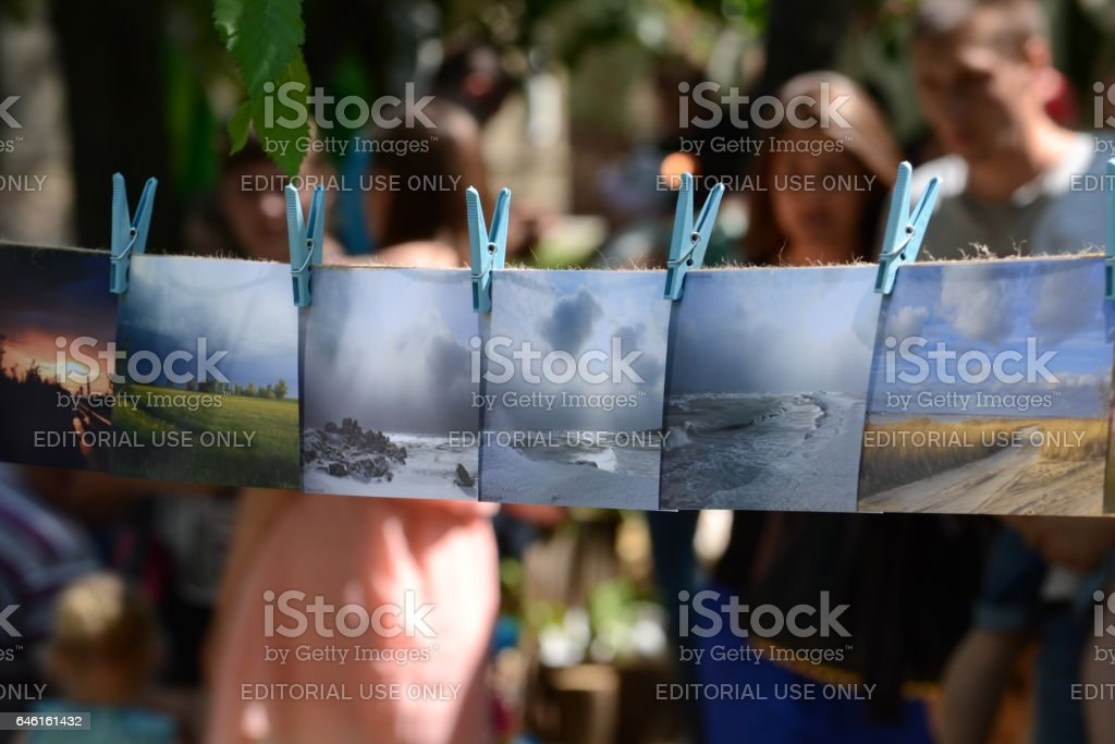 BERDYANSK, UKRAINE - JUNE 5: Public photo exhibition. By photo it is suspended on a rope. Public holiday in the park day of a family on June 5, 2016 in Berdyansk. stock photo