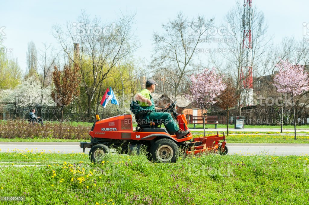 Public service employee mowing the lawn in the city with lawn mower machine vehicle. stock photo