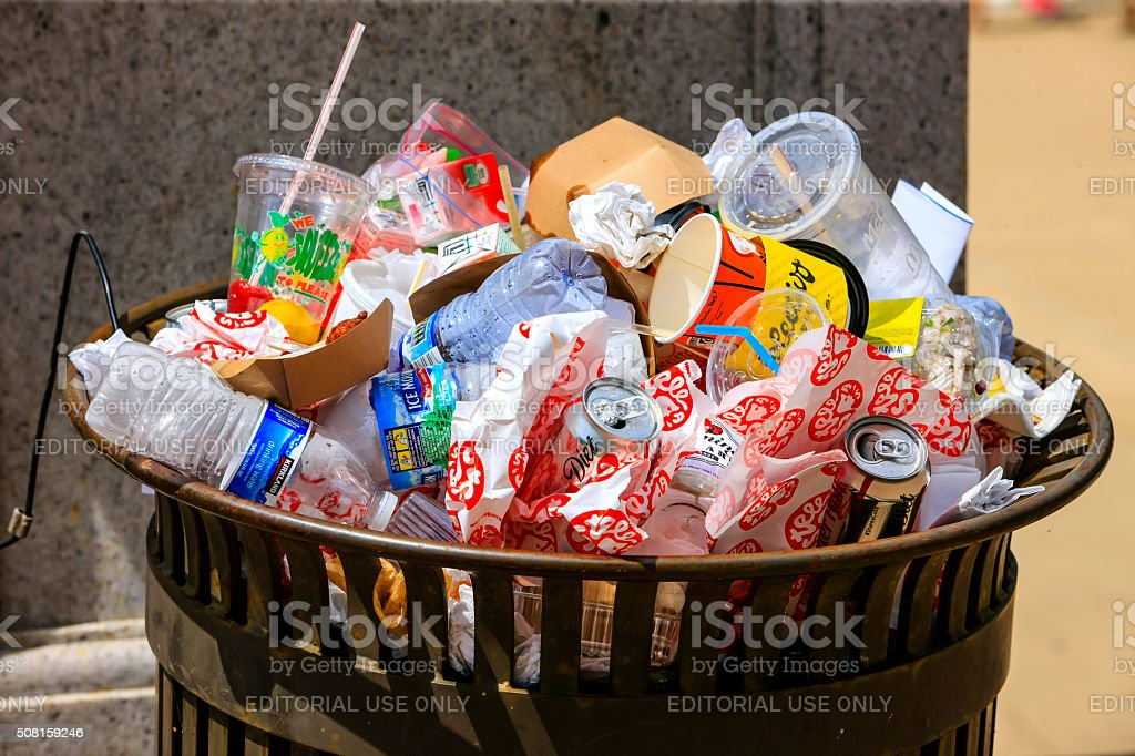 Public trash can overflowing with empty food and drink wrappers stock photo