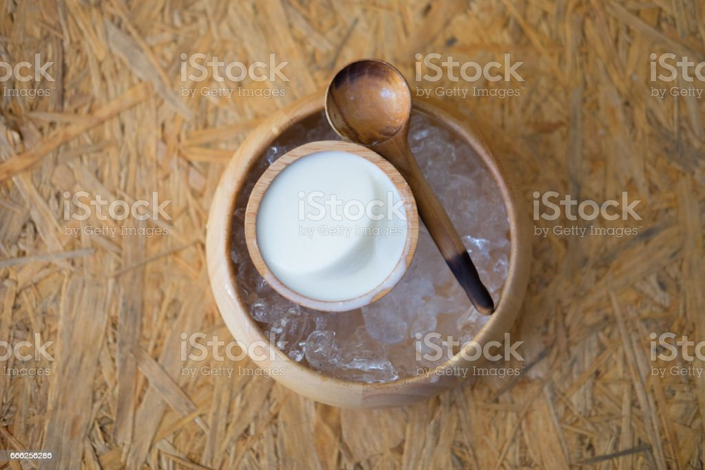 Pudding milk with ice in wooden bowl, top view stock photo