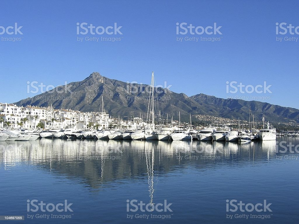 Puerto Banus with its mountains, water, houses, and boats stock photo