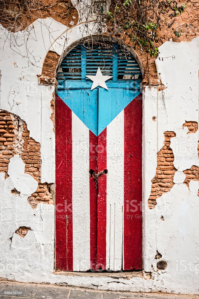 Puerto Rican flag on abandoned building door. stock photo