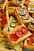 Puff pastry appetizers with vegetables, mushrooms, tomatoes, zucchini and cheese.