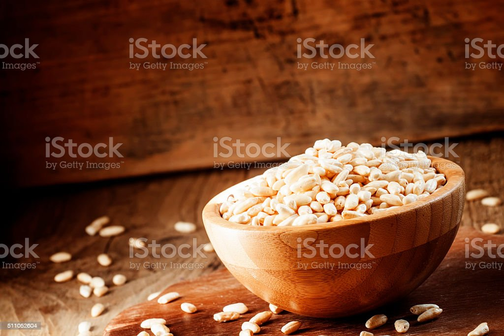 Puffed rice in a wooden bowl stock photo