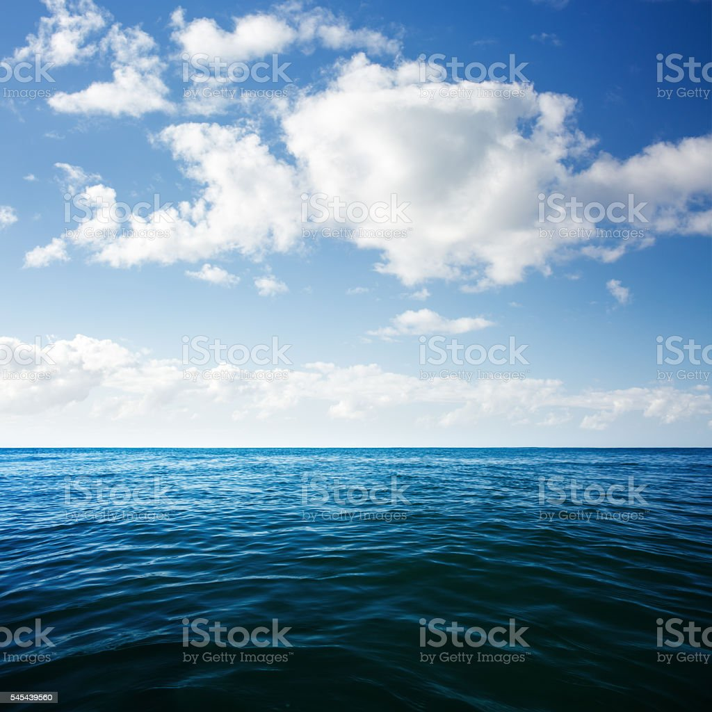 Puffy Clouds over Deep Blue Ocean stock photo