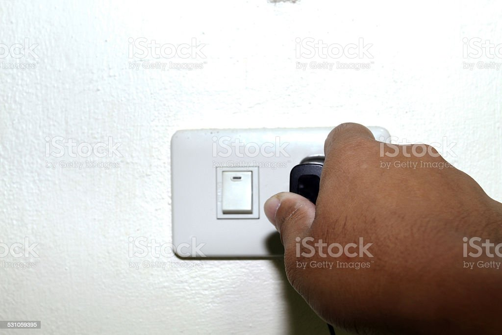 pull the plug concept with man pulling stock photo