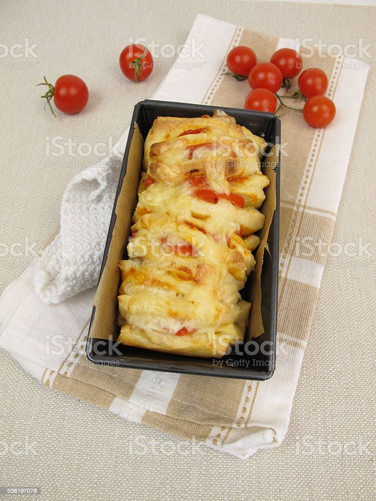 Pull-Apart-Bread with tomatoes and cheese in loaf pan stock photo