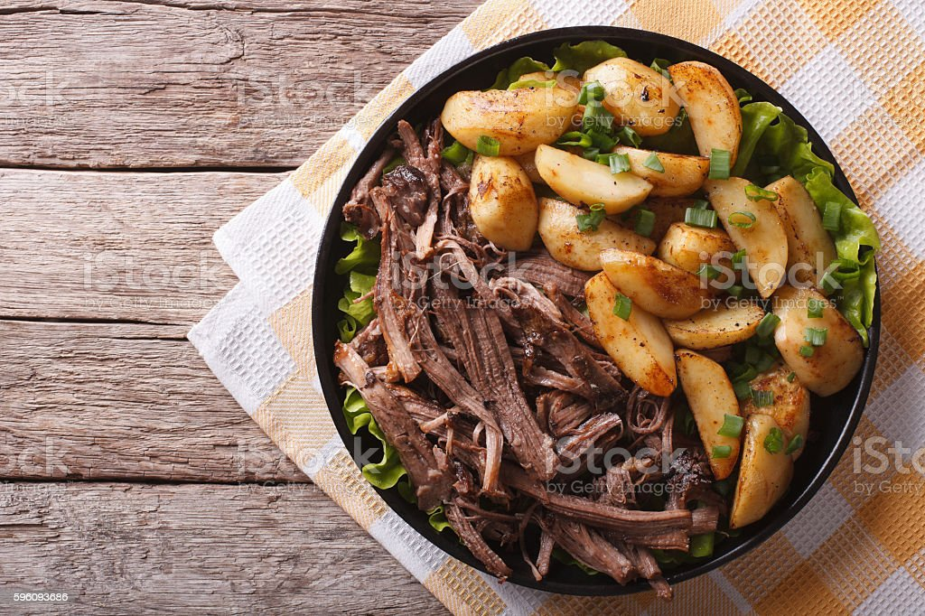 Pulled pork and fried potatoes on plate horizontal top view stock photo