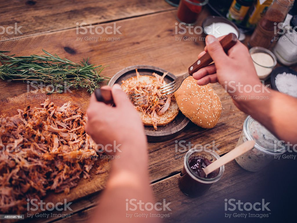 Pulled pork being placed on a burger bun stock photo