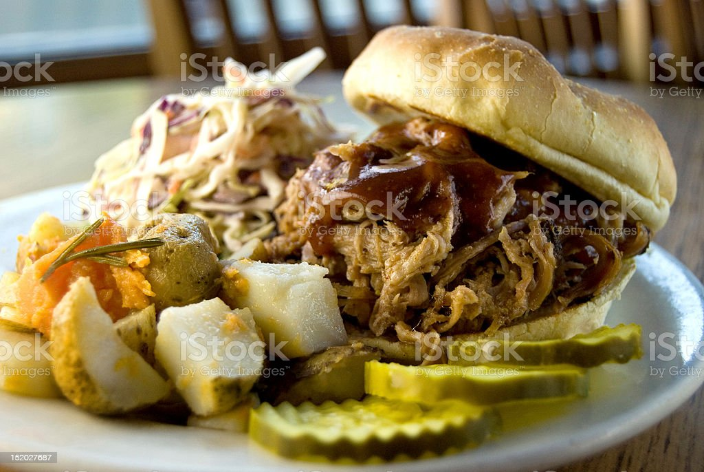 Pulled pork sandwich with yukon gold potatoes, pickles, and coleslaw stock photo