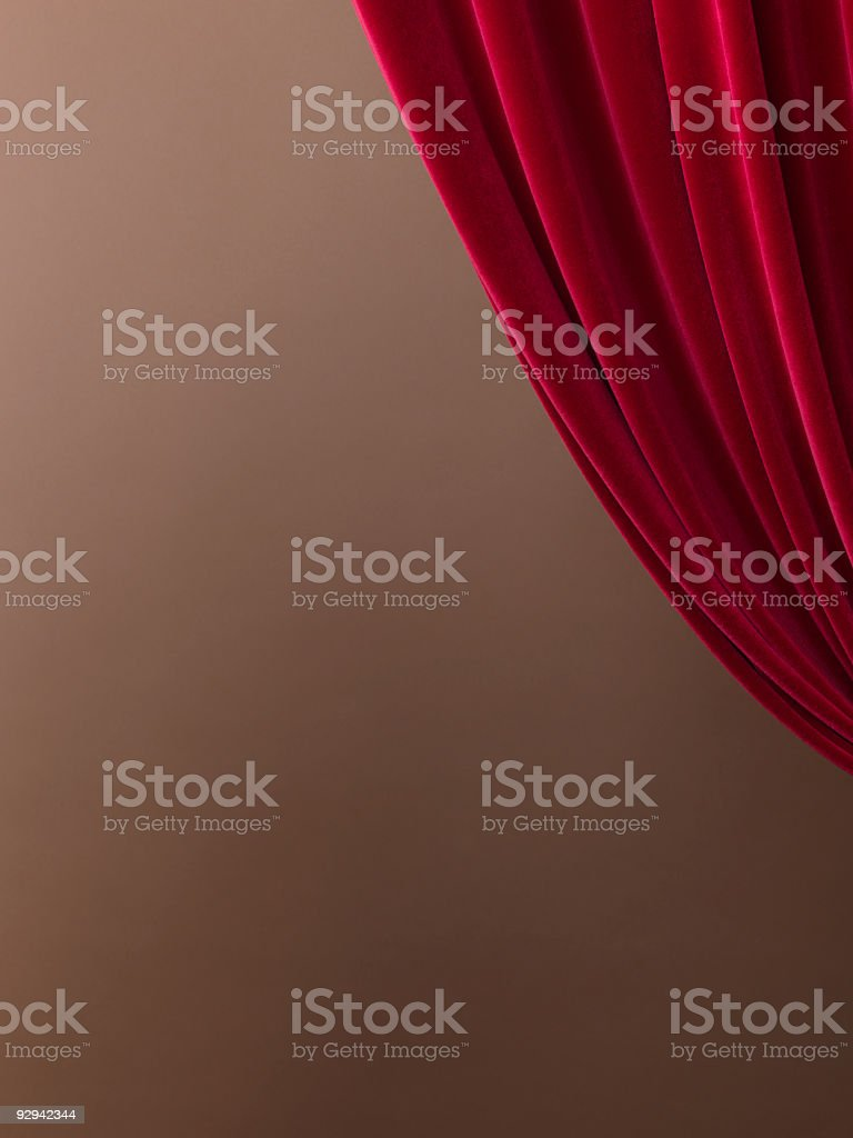 A pulled red velvet curtain with a tan wall stock photo