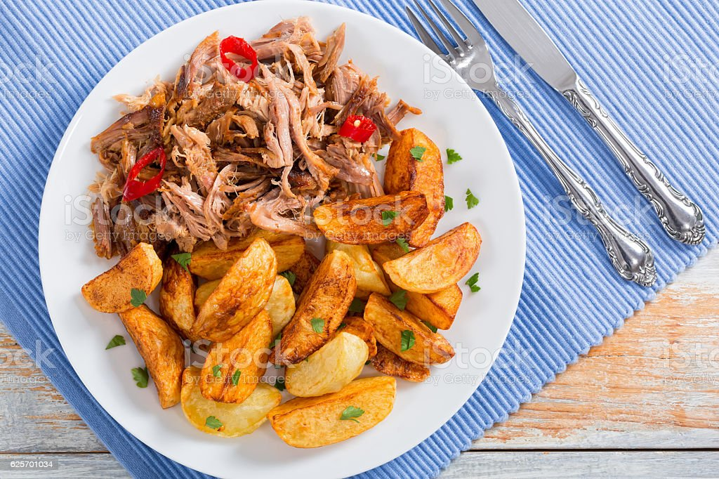 pulled slow-cooked meat grilled in oven with fried potato wedges stock photo