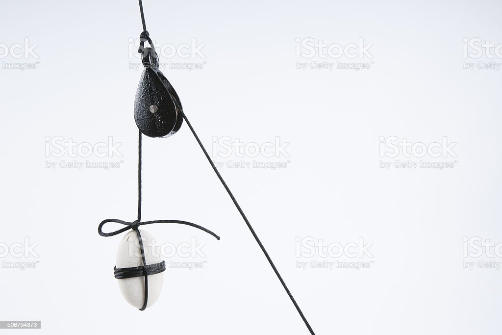 Pulley and a Suspended White Stone. royalty-free stock photo