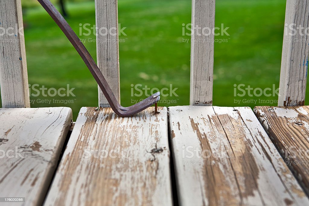 pulling an old nail from deck board stock photo