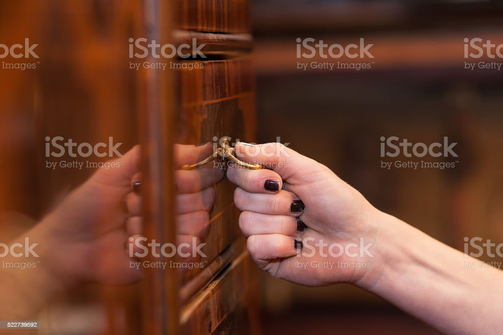 pulling on a drawer knob stock photo