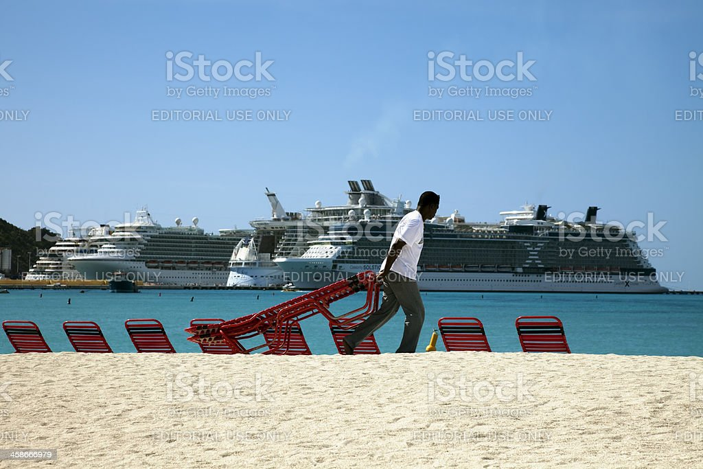 Pulling sun loungers on to the beach stock photo